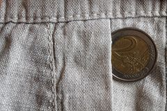 Euro coin with a denomination of 2 euro in the pocket of old linen pants. Euro coin with a denomination of two euro in the pocket of old linen pants Stock Photos