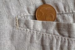 Euro coin with a denomination of 5 euro cents in the pocket of worn linen pants. Euro coin with a denomination of five euro cents in the pocket of worn linen Stock Photos