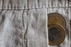 Euro coin with a denomination of one and two euro in the pocket of old linen pants. Euro coin with a denomination of 1 and 2 euro in the pocket of old linen Royalty Free Stock Image