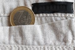 Euro coin with a denomination of one euro in the pocket of linen pants with black stripe Royalty Free Stock Photo