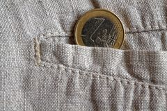 Euro coin with a denomination of 1 euro in the pocket of worn linen pants.  Royalty Free Stock Photography