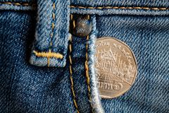 Euro coin with a denomination of twenty euro cents in the pocket of old worn denim jeans.  Royalty Free Stock Photos