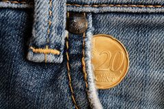 Euro coin with a denomination of twenty euro cents in the pocket of old worn denim jeans.  Stock Photography