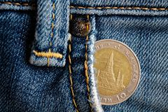 Euro coin with a denomination of twenty euro cents in the pocket of old worn denim jeans.  Royalty Free Stock Image