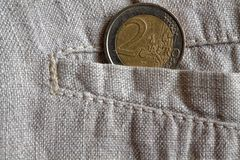 Euro coin with a denomination of 2 euros in the pocket of worn linen pants. Euro coin with a denomination of two euros in the pocket of worn linen pants Stock Photo