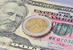 2 Euro Coin on dollar. Close up Euro Coin on dollar banknote stock photos
