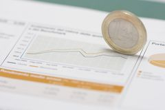 Euro coin on edge and stock market graph Stock Photos