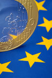 Euro coin on european flag. A Euro coin on an european flag Royalty Free Stock Photo