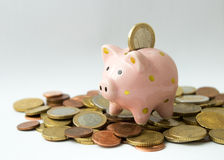 Euro coin falling in piggy bank on top of coin pile Royalty Free Stock Photos