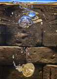 Euro coin falling in a whising well.  Royalty Free Stock Image