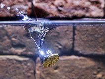 Euro coin falling in a whising well.  Royalty Free Stock Images