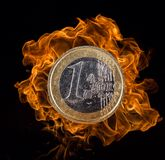 Euro coin with fire flames. Royalty Free Stock Photos