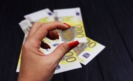 Euro coin in hand of a girl with bills of banknotes stock image