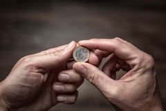 Euro coin held by both hands. One Euro coin held securely by two hands. In front of a dark brown background Stock Images