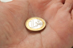 Euro coin on a man�s hand Stock Image