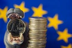 Euro coin in mouth of hippo figurine, EU flag Stock Photos