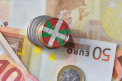 Euro coin with national flag of basque country on the euro money banknotes background. Finance concept Stock Photos