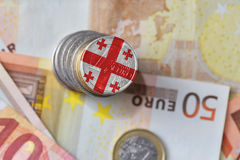 Euro coin with national flag of georgia on the euro money banknotes background. Royalty Free Stock Photos
