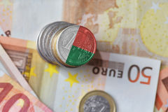 Euro coin with national flag of madagascar on the euro money banknotes background. Finance concept Stock Photos