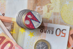 Euro coin with national flag of nepal on the euro money banknotes background. Stock Photo