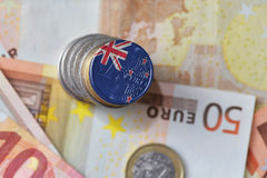 Euro coin with national flag of new zealand on the euro money banknotes background. Finance concept Royalty Free Stock Photos