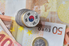 Euro coin with national flag of south korea on the euro money banknotes background. Finance concept royalty free stock images