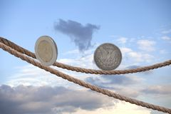 2 Euro coin and one dollar coin balancing on rope. In the sky royalty free stock photography