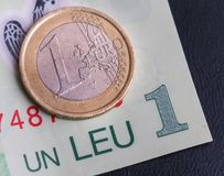 1 euro coin over 1 leu RON bill. S symbolizing the rate exchange supremacy of the european currency Stock Images