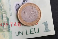 1 euro coin over 1 leu RON bill. S symbolizing the rate exchange supremacy of the european currency Stock Image