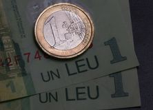 1 euro coin over 1 leu RON bills. Symbolizing the rate exchange supremacy of the european currency Royalty Free Stock Images