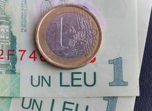 1 euro coin over 1 leu RON bills. Symbolizing the rate exchange supremacy of the european currency Royalty Free Stock Photo