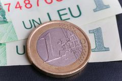 1 euro coin over 1 leu RON bills. Symbolizing the rate exchange supremacy of the european currency Stock Images
