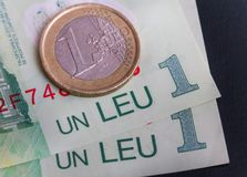 1 euro coin over 1 leu RON bills. Symbolizing the rate exchange supremacy of the european currency Stock Image