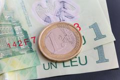 1 euro coin over 1 leu RON bills. Symbolizing the rate exchange supremacy of the european currency Stock Photos