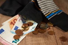 Hiding money in socks is an insecure investment. Euro coin and paper currency falling out of money sock Stock Images
