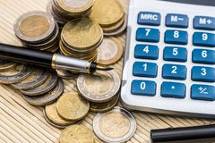 Euro coin with pen and calculator. Close up Stock Photography