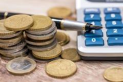 Euro coin with pen and calculator. On desk Stock Photos