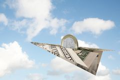 Euro coin riding dollar plane. Euro coin flying away on a dollar bill paper plane Royalty Free Stock Image