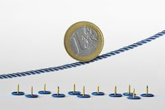 Euro coin on rope over push pins - Concept of upward trend of euro currency and euro currency risk. Euro coin on rope over push pins. Concept of upward trend of royalty free stock photo