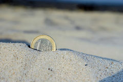 Euro coin in the sand. Lost money summer, sunny, symbol Royalty Free Stock Images