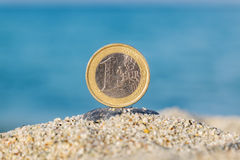 Euro coin in the sand. One Euro coin in the sand against blue sea Royalty Free Stock Photo