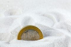 Euro coin in sand. Euro coin placed in white sand royalty free stock photos