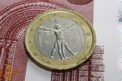 Euro coin standing on paper money. Macro photo of an euro coin standing on paper money. The Vitruvian Man surrounded by euro stars is highly visible on the coin royalty free stock photo