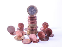 1 Euro coin standing on top of stack of euro coins surrounded by smaller value standing coins Royalty Free Stock Images