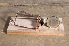 Euro coin in a trap. Euro coin in a wooden mousetrap on a table Stock Image