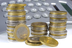 Euro coins. Stacked euro coins and financial calculator stock photo
