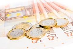 Euro coins on 50-euro banknotes. Detail of some euro coins on 50-euro banknotes on white background Royalty Free Stock Photo