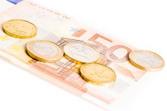 Euro coins on 50-euro banknotes Stock Photos