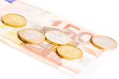 Euro coins on 50-euro banknotes. Detail of some euro coins on 50-euro banknotes on white background Stock Photos