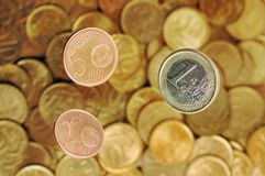 Euro coins. Coins in the denomination of two, five cent and one euro fall to heaps of money Stock Photo